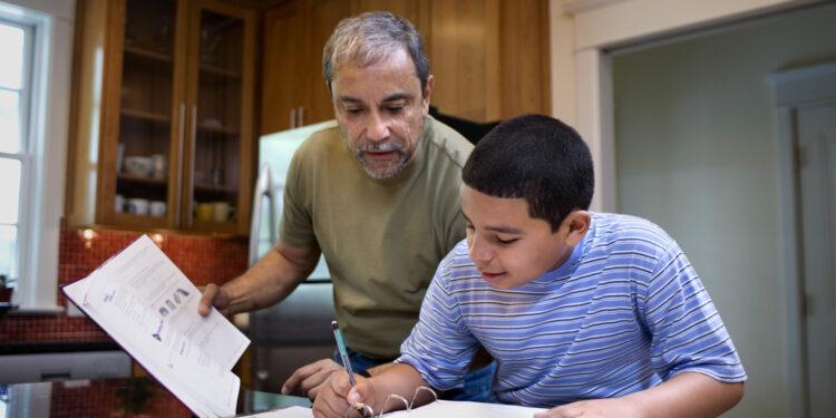 Grandfather helping boy with homework